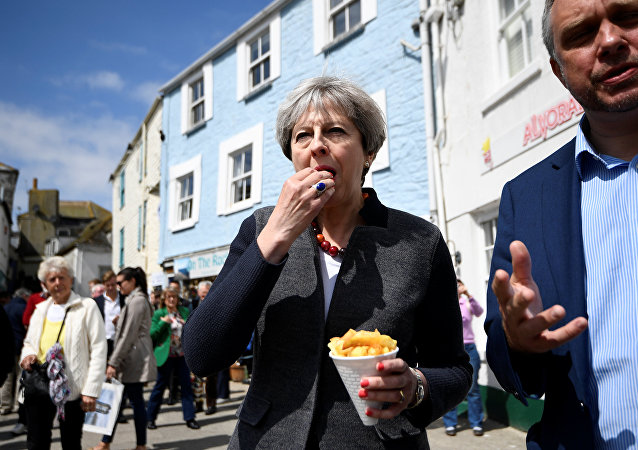Britain's Prime Minister Theresa May enjoys some chips during a campaign stop in Mevagissey, Cornwall, May 2, 2017