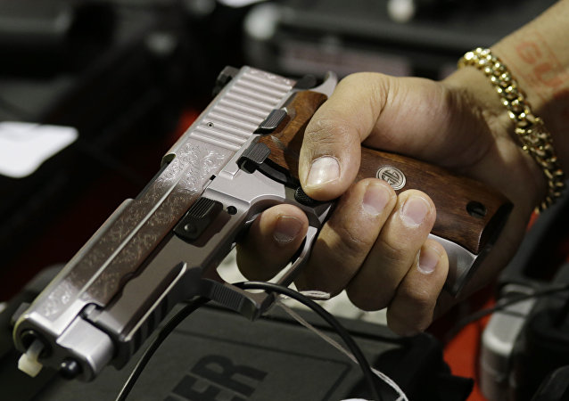 A customer looks at a SIG Sauer hand gun at a gun show held by Florida Gun Shows, Saturday, Jan. 9, 2016, in Miami.