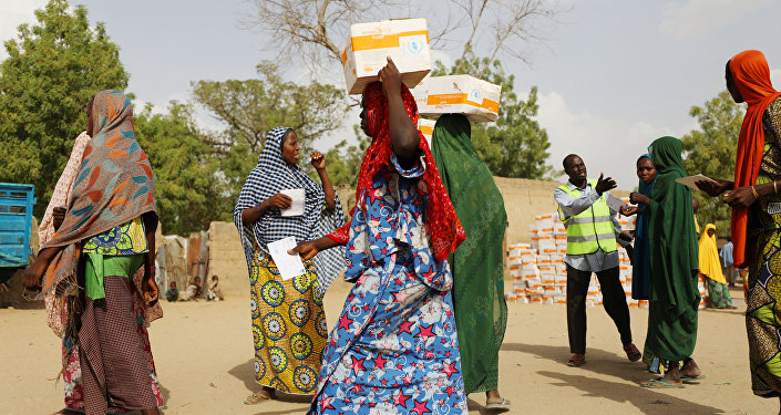 Women carry food supplement received from World Food Programme (WFP) at the Banki IDP camp, in Borno, Nigeria April 26, 2017