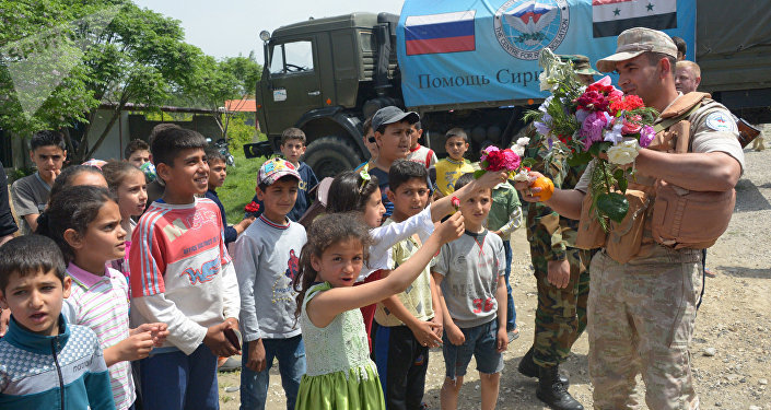 Children in the village of Brabishbo, Syria greet Russian servicemen with flowers and citrus fruit
