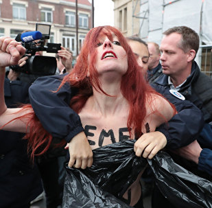 Police cover the chest of a member of feminist activist group Femen as they arrest her after unveiling a banner on a church in Henin-Beaumont, north-western France, to protest against French presidential election candidate for the far-right Front National (FN - National Front) party Marine Le Pen on May 7, 2017, during the second round of the Presidential election.