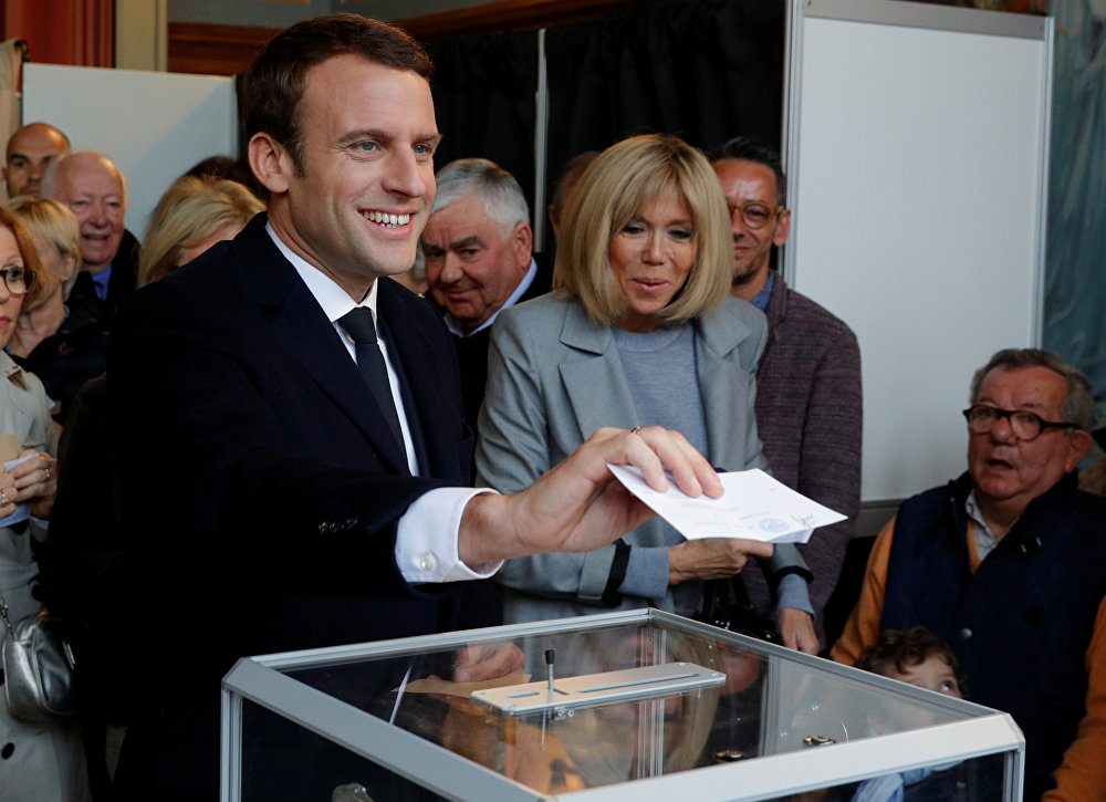 Emmanuel Macron (L), head of the political movement En Marche !, or Onwards !, and candidate for the 2017 French presidential election, casts his ballot in the first round of 2017 French presidential election at a polling station in Le Touquet, northern France, April 23, 2017. At C, his wife Brigitte Trogneux.