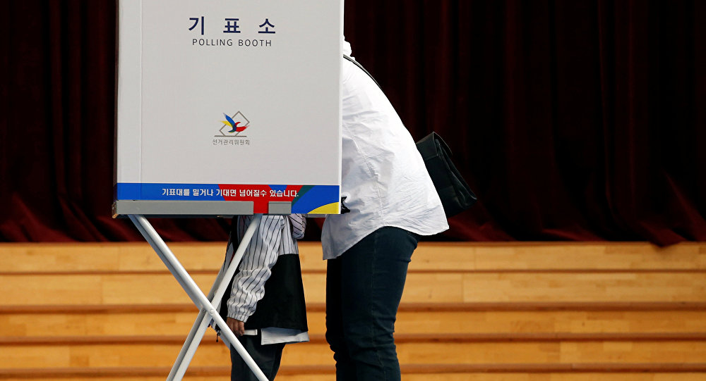 A voter and her son are seen at a polling station during the presidential elections in Seoul, South Korea May 9, 2017.