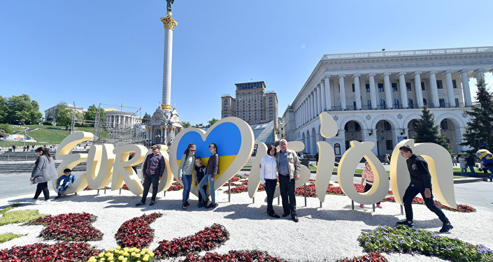 People pose for pictures in front of the official logo for the Eurovision Song Contest on Independence Square in Kiev on May 3, 2017.