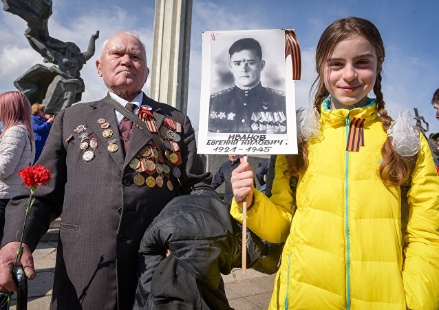 A World War II veteran and a girl attend festivities at the Victory Monument as Latvia's large Russian minority marks 72 years since the end of World War II and commemorates the Soviet victory over Nazi Germany in Riga, Latvia