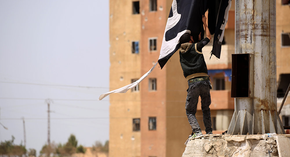 A member of the US-backed Syrian Democratic Forces (SDF), made up of an alliance of Arab and Kurdish fighters, removes an Islamic State group flag in the town of Tabqa, about 55 kilometres (35 miles) west of Raqa city, on April 30, 2017, as they advance in their battle for the group's de facto capital