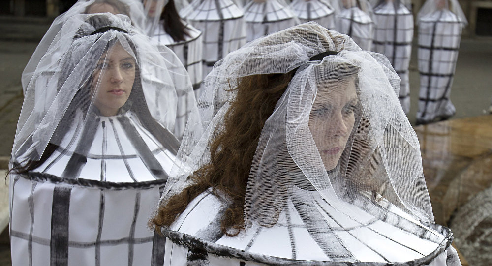 Students dressed as caged brides to raise awareness to the risks of human trafficking and sexual exploitation