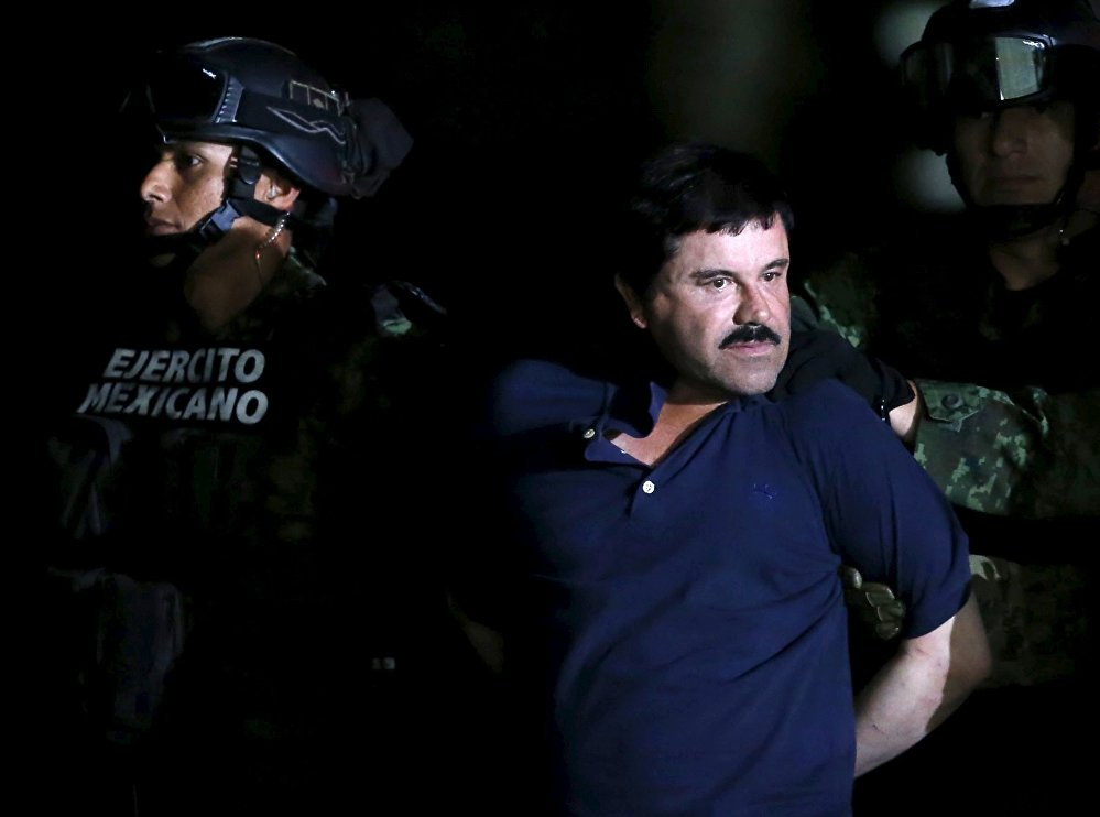 Recaptured drug lord Joaquin El Chapo Guzman is escorted by soldiers during a presentation in Mexico City, January 8, 2016