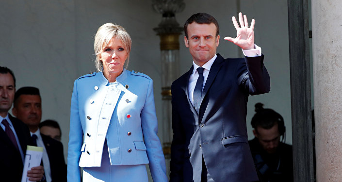 French President Emmanuel Macron and his wife Brigitte Trogneux wave to French President Francois Hollande (not pictured) as he leaves after the handover ceremony at the Elysee Palace in Paris, France, May 14, 2017