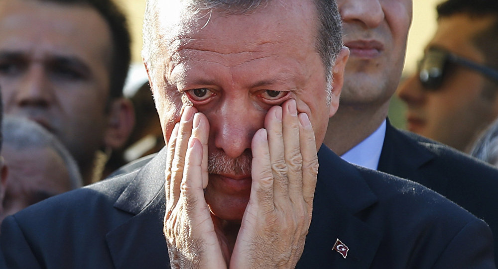 Turkish President Recep Tayyip Erdogan, right, wipes his tears