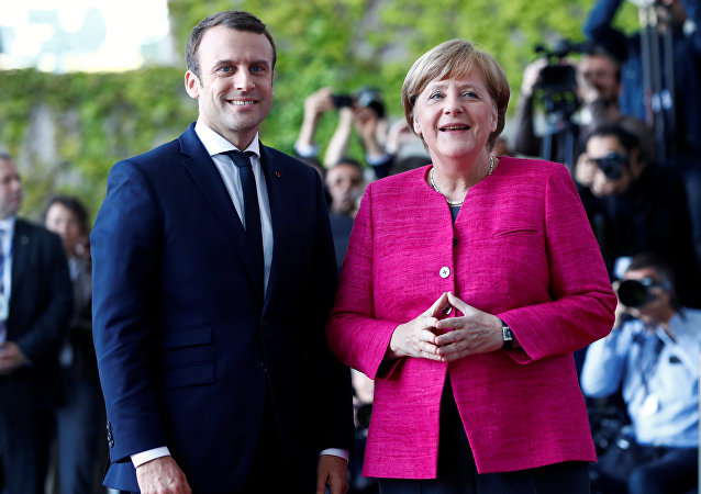 German Chancellor Angela Merkel and French President Emmanuel Macron arrive at a ceremony at the Chancellery in Berlin, Germany, May 15, 2017.