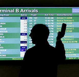 A person points to a screen with an airplane travel list while holding up a phone at Newark Liberty International Airport, in Newark, N.J.