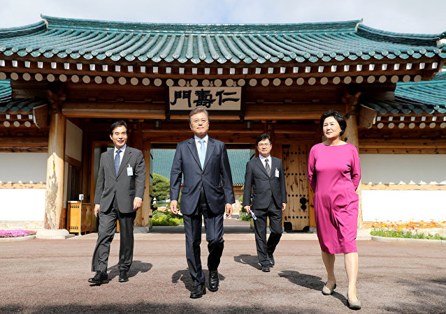 South Korean President Moon Jae-in leaves his residence as the First Lady Kim Jung-sook looks on at the Presidential Blue House in Seoul, South Korea, May 15, 2017.
