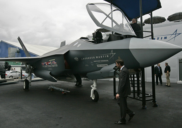 People wander around a life-size model of US planemaker Lockheed Martin's F-35 Lightning II 5th generation fighter plane during the Farnborough aerospace show, in Farnborough, England
