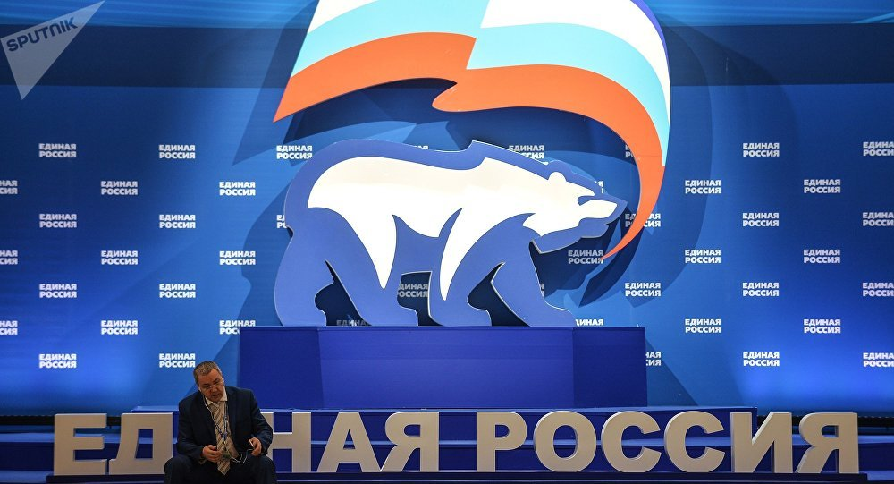 A man is seen here sitting next to a stand with United Russia symbols (File)