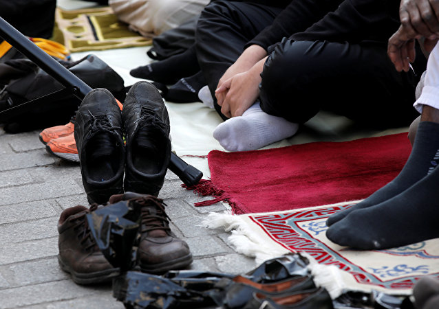 Shoes are pictured as Muslims pray during Friday prayers in the street in front of the city hall of Clichy, near Paris, France, April 21, 2017, after an unauthorised place of worship was closed by local authorities