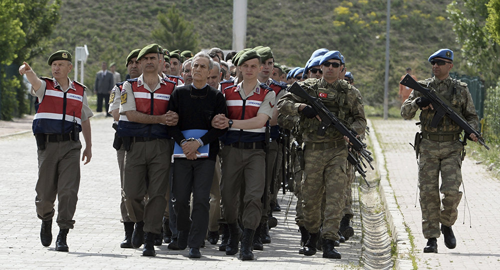 Paramilitary police officers and commandos escort the alleged main ringleaders of last summer's failed military coup before their trial at a courthouse in the outskirts of Ankara, Turkey, Monday, May 22, 2017. Paramilitary police officers and commandos escort the alleged main ringleaders of last summer's failed military coup before their trial at a courthouse in the outskirts of Ankara, Turkey, Monday, May 22, 2017. The black-shirted man in front is Akin Ozturk, former Turkish Air Force commander and suspected coup mastermind.