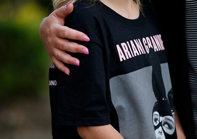 A youngster wearing a t-shirt showing U.S. singer Ariana Grande talks to the media near the Manchester Arena in Manchester, Britain May 23, 2017.