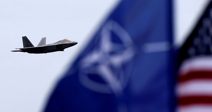 NATO and US flags flutter as U.S. Air Force F-22 Raptor fighter flies over the military air base in Siauliai, Lithuania, April 27, 2016.
