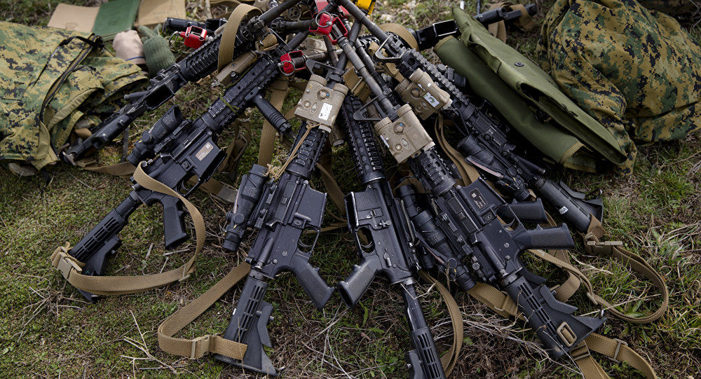 Assault rifles belonging to US Marines are piled on the ground