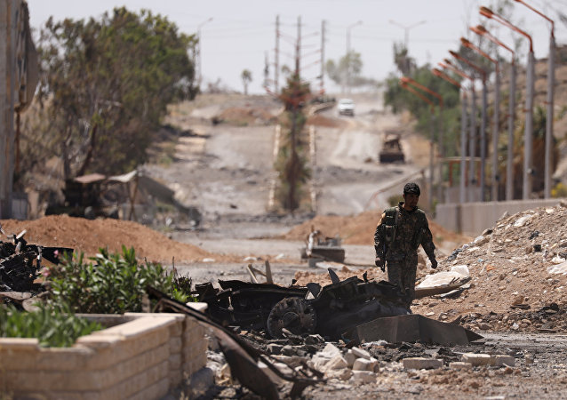 A Syrian Democratic Forces (SDF) fighter walks through a damaged street in the town of Tabqa, after SDF captured it from Islamic State militants this week, in Raqqa, Syria May 12, 2017