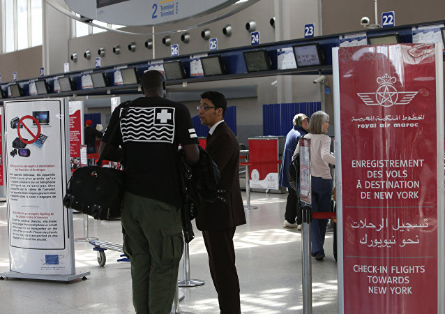 Airport staff inform passengers at the entrance to the Casablanca - New York flight checkpoint at Casablanca Mohammed V International Airport on Thursday, March 29, 2017