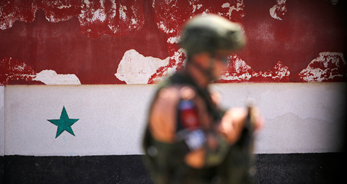 A Russian soldier stands guard near a Syrian national flag drawn on the wall