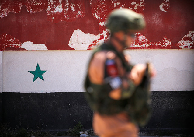 A Russian soldier stands guard near a Syrian national flag drawn on the wall as rebel fighters and their families evacuate the besieged Waer district in the central Syrian city of Homs, after an agreement reached between rebels and Syria's army, Syria May 21, 2017