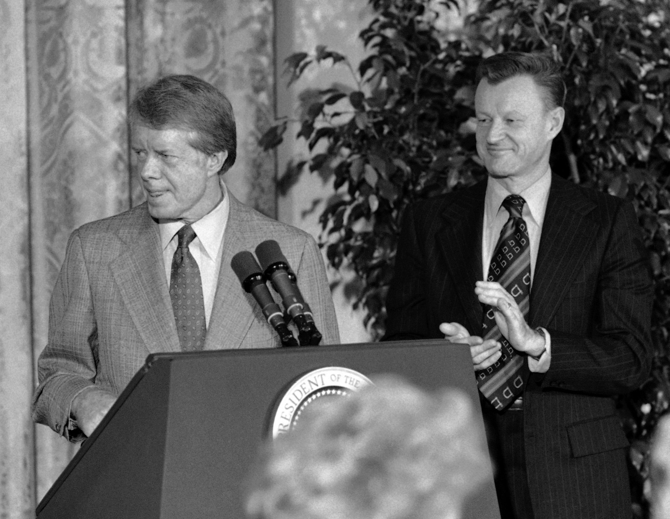 President Jimmy Carter, claiming success for his human rights policies, is applauded by aides Zbigniew Brzezinski and Anne Wexler in Washington, Dec. 6, 1978