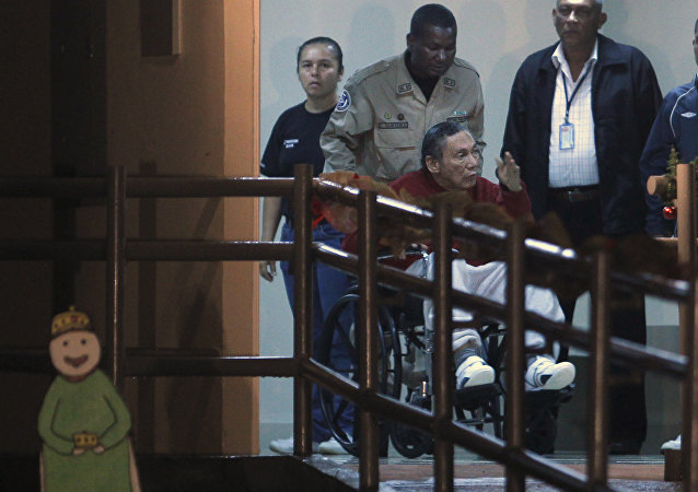 Panama's ex-dictator Manuel Noriega gestures while being carried in a wheelchair by a police officer inside El Renacer prison in the outskirts of Panama City, Sunday, Dec. 11, 2011