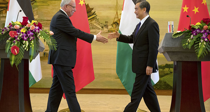 Palestinian Foreign Minister Riyad Al-Maliki, left, and Chinese Foreign Minister Wang Yi reach to shake hands at the end of their joint press conference at the Ministry of Foreign Affairs in Beijing, Thursday, April 13, 2017.