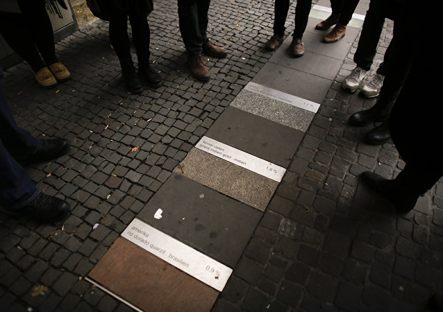 In this photo taken Sunday, Oct. 9, 2016 people stand around the public art piece 'Meinstein' (My Stone), by Nadia Kaabi-Linke, which shows the percentage of migrants in the district of Neukoelln with different stones, during a so called 'Refugee Tour' by Syrian refugee Firas Zakri trough Neukoelln in Berlin, Germany