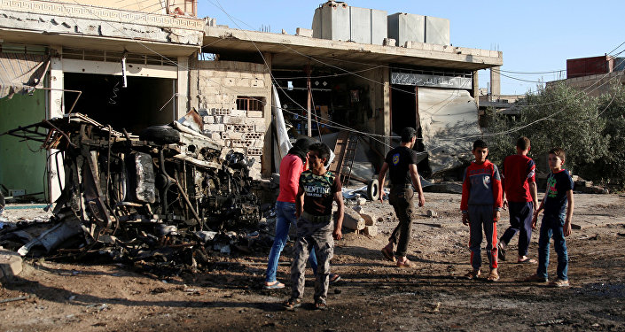People walk at a site hit by an airstrike in the rebel-held Tafas town, in Deraa Governorate, Syria June 5, 2017