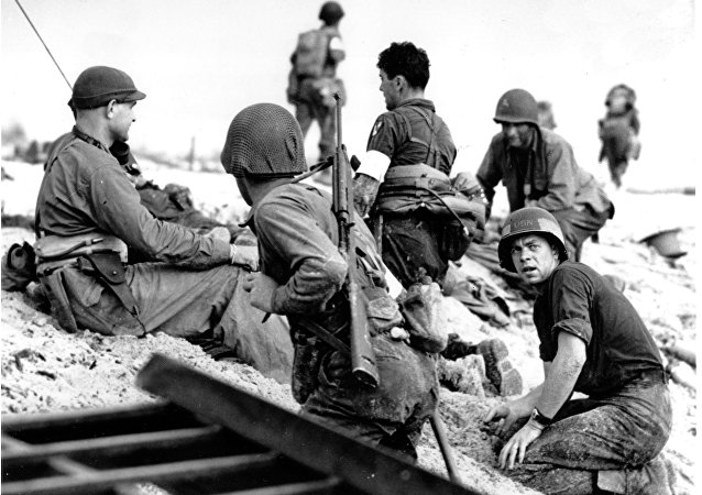 In this June 6, 1944 file photo, first wave beach battalion Ducks lay low under the fire of Nazi guns on the beach of southern France on D-Day, June 6, 1944 during World War II. One invader operates a walkie talkie radio directing other landing craft to the safest spots for unloading their parties of fighting men.