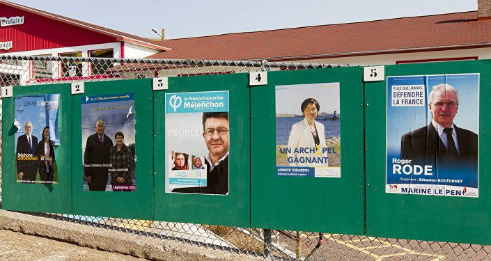 Campaign posters for the French legislative elections are displayed outside a polling station in the French overseas territory of Saint-Pierre