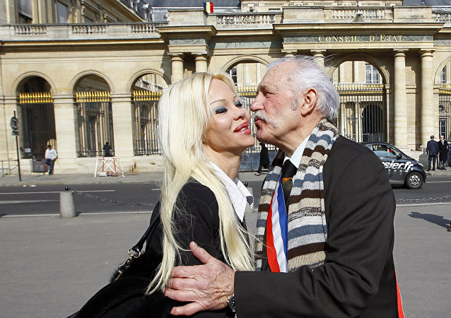 Isabelle Laeng, known as Cindy Lee, left, of the Pleasure Party campaigning for France's upcoming presidential election, kisses Roger Lagache, right, French Major of a northern village of Tollent, in front of the France's Conseil d'Etat in Paris, France. (File)