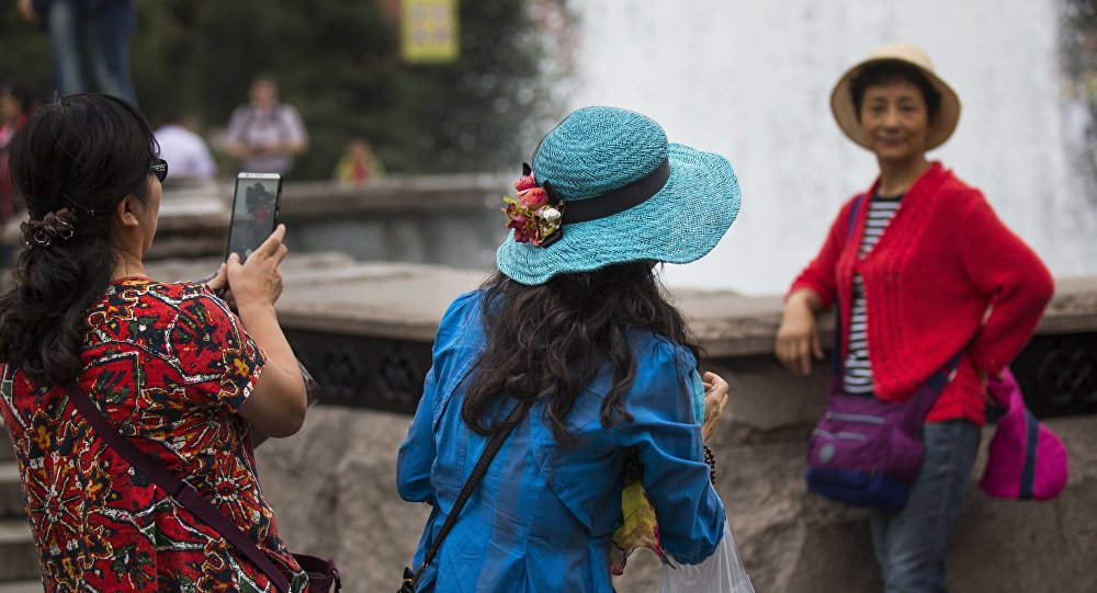 Chinese tourists make photos at a fountain just off Red Square in Moscow, Russia