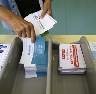Voter picks up ballots at a polling station before voting for the first round of parliamentary elections in Marseille, southern France, Sunday, June 11, 2017