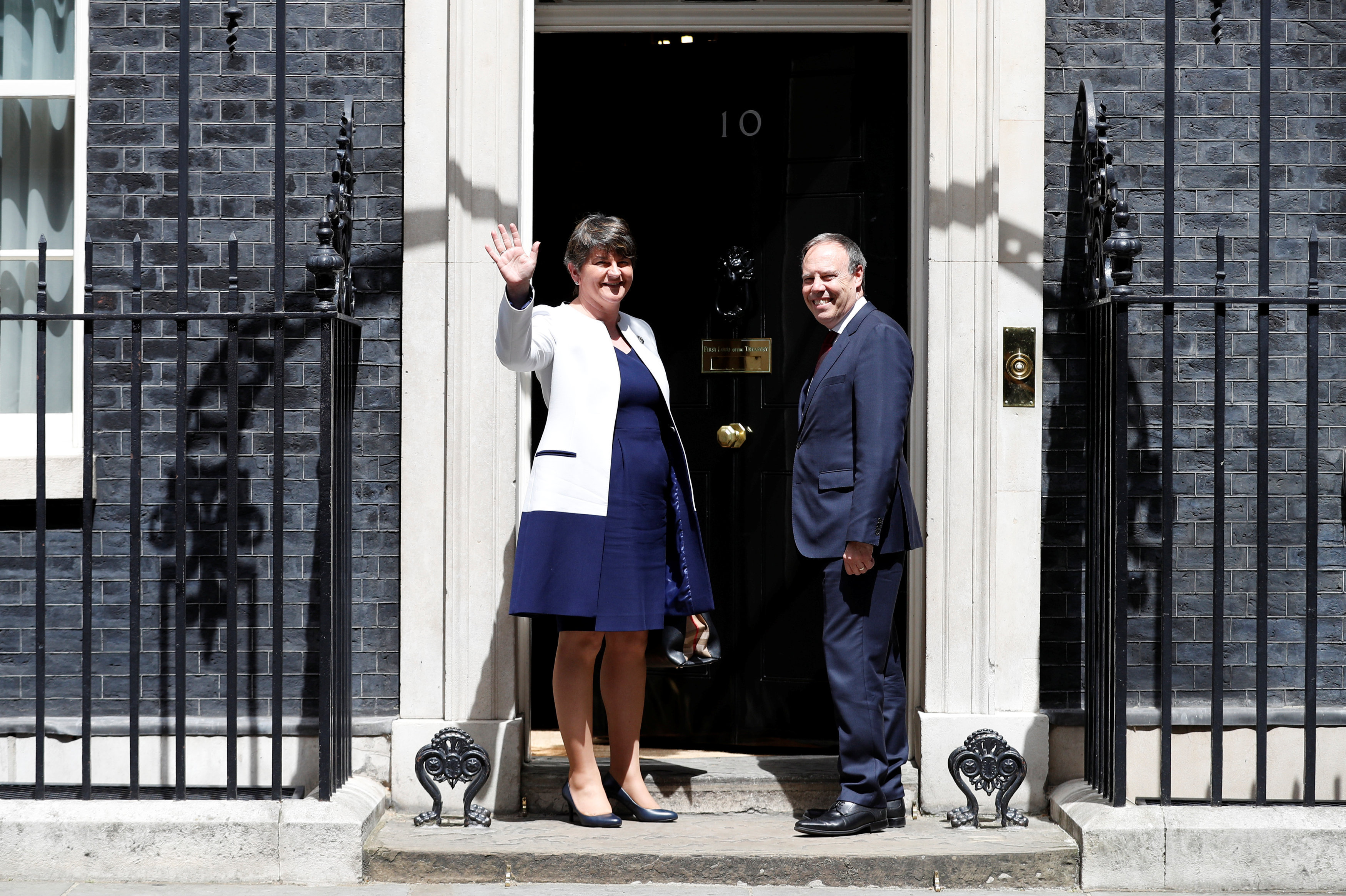 The leader of the Democratic Unionist Party (DUP), Arlene Foster, and the Deputy Leader Nigel Dodds, stand on the steps of 10 Downing Street before talks with Britain's Prime Minister Theresa May, in central London, Britain June 13, 2017