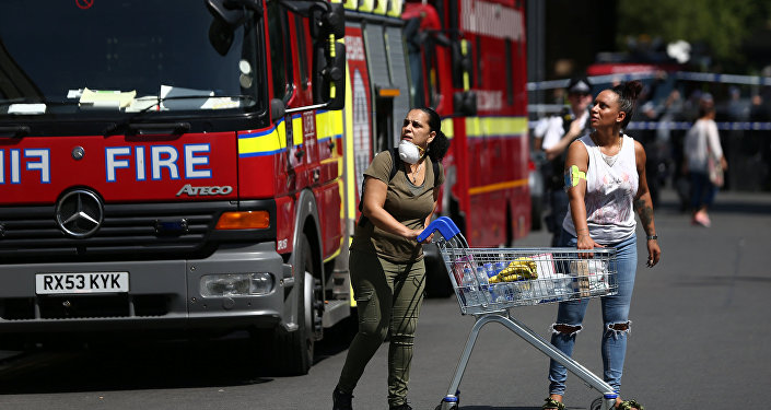 People react near a tower block severely damaged by a serious fire, in north Kensington, West London, Britain June 14, 2017.