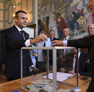 French President Emmanuel Macron casts his ballot as he votes at a polling station in Le Touquet, northern France, during the second round of the French parliamentary elections (elections legislatives in French)