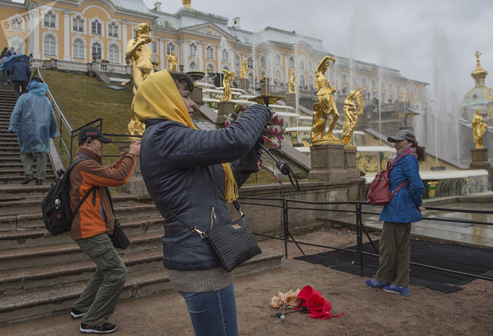 Tourists pose for photographs against the background of the Grand Cascade fountains during the opening of the summer season at the Peterhof museum-reserve