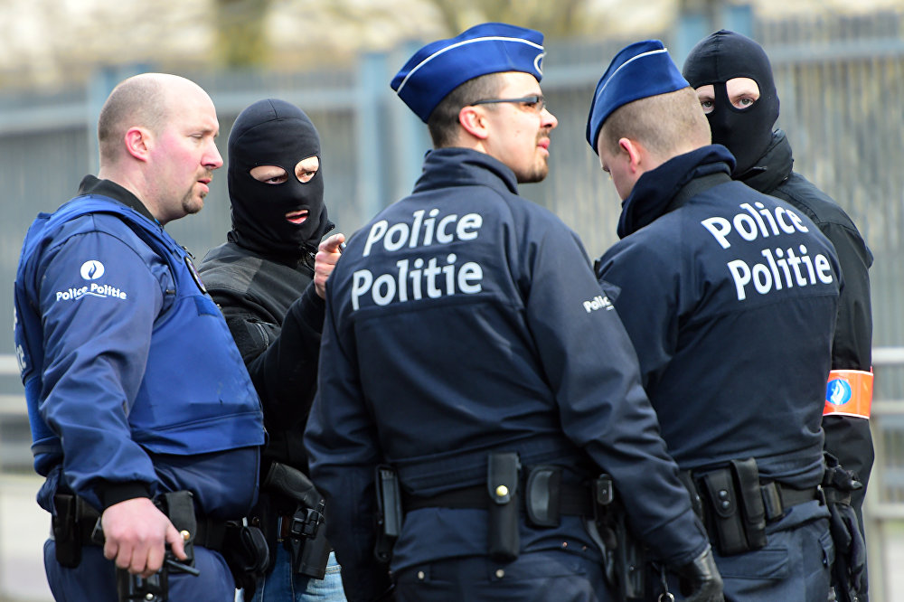 Policemen speak at a security perimeter near Maalbeek metro station, on March 22, 2016 in Brussels, after a blast at this station near the EU institutions caused deaths and injuries
