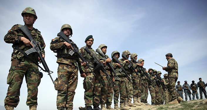 In this Mar. 15, 2016 file photo, Afghanistan's National Army soldiers stand guard, following weeks of heavy clashes to recapture the area from Taliban militants in Dand-e Ghouri district in Baghlan province, north of Kabul, Afghanistan