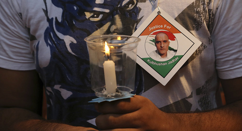 An Indian man holds a candle as he participates in a demonstration in support of Indian naval officer Kulbhushan Jadhav in Mumbai, India, Saturday, June 03, 2017