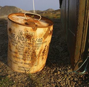 Rusty container of lubricant oil for a U.S. military vehicle stands among abandoned U.S. military material on Aug. 16, 2005, outside the eastern Greenland settlement of Kulusuk where there used to be an U.S. Air Force base as part of an early warning radar system (File)