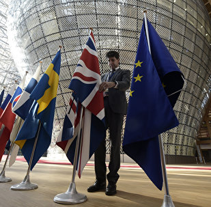 An organiser adjusts the British national flag on April 29, 2017, prior to the EU leaders summit at the Europa building, the main headquarters of European Council and the Council of the EU, in Brussels
