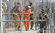 A detainee from Afghanistan is led by military police with his hands chained at Camp X-Ray at the U.S. Naval Base in Guantanamo Bay, Cuba, in this Feb. 2, 2002, file photo