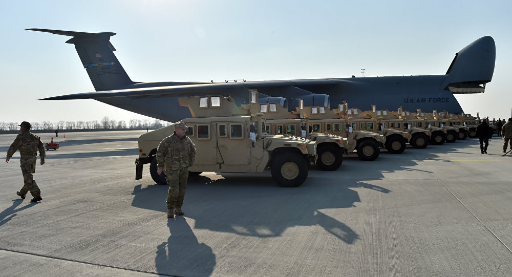 Ukrainian servicemen walk in front of armoured cars at Kiev airport on March 25, 2015 during a welcoming ceremony of the first US plane delivery of non-lethal aid, including 10 Humvee vehicles.