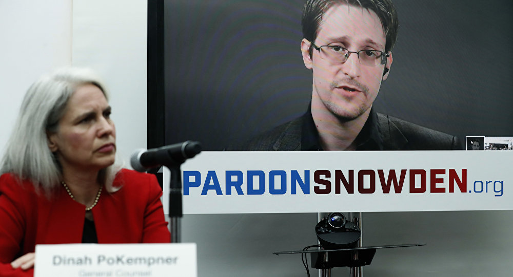 Dinah PoKempner, left, general council for Human Rights Watch, listens as Edward Snowden speaks on a television screen via video link from Moscow during a news conference to call upon President Barack Obama to pardon Snowden before he leaves office, Wednesday, Sept. 14, 2016, in New York.